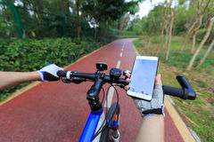 Cyclist use smartphone for navigation. When riding mountain bike on forest trail Royalty Free Stock Image