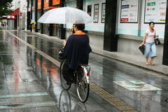 Cyclist Using an Umbrella moves along sidewalk in Japan Royalty Free Stock Images