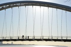 Cyclist and walker in silhouette on Humber Bay Arch Bridge. A cyclist moves east past a stationary walker paused to view the Toronto skyline in early morning Stock Photos