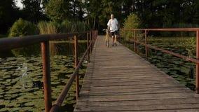Cyclist walking over the bridge stock video