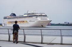 Cyclist watches cruise ship Royalty Free Stock Image