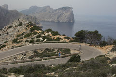 Cyclist on winding mountain road. With sea behind Stock Images