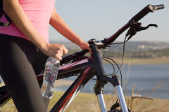 Cyclist woman with bottle of water. Woman on bicycle with bottle of water closeup Stock Photography