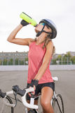 Cyclist woman takes a water break Royalty Free Stock Photography