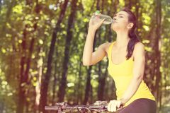 Cyclist young woman in yellow t-shirt outdoors drinking bottled water Stock Photo