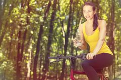 Cyclist young woman in yellow t-shirt outdoors drinking bottled water Royalty Free Stock Photo