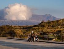 Cycliste arrêté au parking de Kusasenri avec émettre de la vapeur le cratère de Nakadake au fond après 2016 image libre de droits