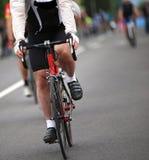 cycliste avec la veste protégeant du vent pendant la course de recyclage dans la ville Images stock