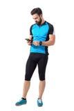 Cycliste barbu dans les vêtements de sport dactylographiant sur son smartphone images stock