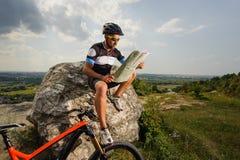 Cycliste beau avec la carte d'itinéraire sur le dessus de la roche Image stock