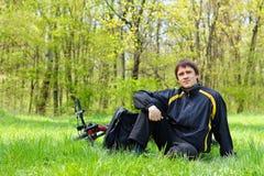Cycliste d'homme s'asseyant sur l'herbe verte Image stock