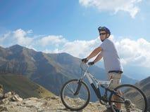 Cycliste dans l'environnement de montagnes Photographie stock
