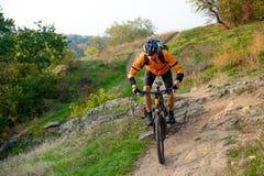 Cycliste dans l'orange montant le vélo de montagne sur Autumn Rocky Trail Sport extrême et concept faisant du vélo d'Enduro photo libre de droits