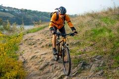 Cycliste dans l'orange montant le vélo de montagne sur Autumn Rocky Trail Sport extrême et concept faisant du vélo d'Enduro photographie stock libre de droits