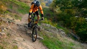 Cycliste dans l'orange montant le vélo de montagne sur Autumn Rocky Trail Sport extrême et concept faisant du vélo d'Enduro images stock
