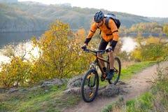 Cycliste dans l'orange montant le vélo de montagne sur Autumn Rocky Trail Sport extrême et concept faisant du vélo d'Enduro photographie stock