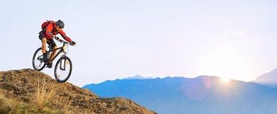 Cycliste dans l'?quitation rouge le v?lo en bas de la roche au lever de soleil Sport extr?me et concept faisant du v?lo d'Enduro photo stock