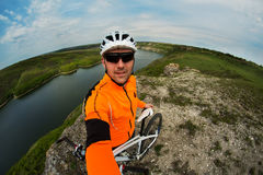 Cycliste dans l'usage orange montant le vélo au-dessus de la rivière Photo libre de droits