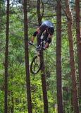 Cycliste de cascade de style libre dans le plein vol avec des arbres à l'arrière-plan Photos stock