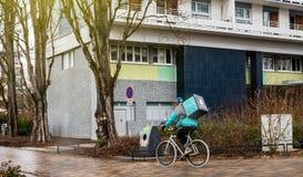 Cycliste de Deliveroo le jour pluvieux travaillant dur pour livrer sur le foo de temps Photographie stock libre de droits