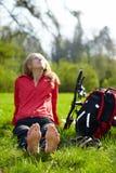 Cycliste de fille appréciant nu-pieds la relaxation se reposant dans l'herbe verte fraîche photographie stock libre de droits
