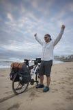 Cycliste de fond sur la plage avec des bras dans le ciel photos stock