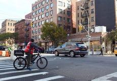 Cycliste de la livraison attendant à la lumière rouge dans la cuisine du ` s d'enfer Image libre de droits
