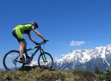 Cycliste de montagne contre le contexte des montagnes neigeuses Photos libres de droits