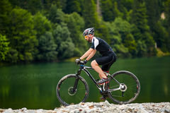 Cycliste de montagne sur des traînées Photographie stock libre de droits