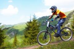 Cycliste de montagne sur le rce incliné Photographie stock