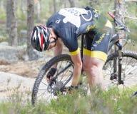 Cycliste de vélo de montagne fixant un pneu crevé dans la forêt Photos stock