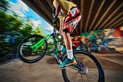 Cycliste de vélo de montagne faisant le cascade de wheelie sur un vélo de foule sur une voie de pompe Photos libres de droits