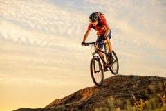 Cycliste en rouge montant le vélo en bas de la roche au coucher du soleil Sport extrême et concept faisant du vélo d'Enduro Photographie stock