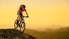 Cycliste en rouge montant le vélo en bas de la roche au coucher du soleil Sport extrême et concept faisant du vélo d'Enduro Photos stock