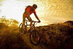 Cycliste en rouge montant le vélo sur Autumn Rocky Trail au coucher du soleil Sport extrême et concept faisant du vélo d'Enduro Images stock