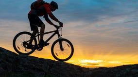 Cycliste en rouge montant le vélo sur Autumn Rocky Trail au coucher du soleil Sport extrême et concept faisant du vélo d'Enduro Photo stock