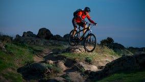 Cycliste en rouge montant le vélo sur Autumn Rocky Trail au coucher du soleil Sport extrême et concept faisant du vélo d'Enduro Images libres de droits