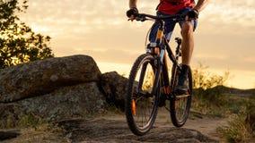 Cycliste en rouge montant le vélo sur Rocky Trail au coucher du soleil Sport extrême et concept faisant du vélo d'Enduro Photos libres de droits