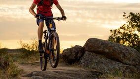Cycliste en rouge montant le vélo sur Rocky Trail au coucher du soleil Sport extrême et concept faisant du vélo d'Enduro Photographie stock libre de droits