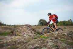 Cycliste en rouge montant le vélo sur Rocky Trail au coucher du soleil Sport extrême et concept faisant du vélo d'Enduro Image libre de droits