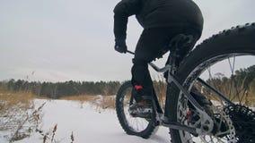 Cycliste extrême professionnel de sportif montant le gros vélo dans l'extérieur Le tour de cycliste en hiver dans le domaine de n clips vidéos