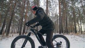 Cycliste extrême professionnel de sportif montant un gros vélo dans l'extérieur Le tour de cycliste chez l'homme de forêt de neig banque de vidéos