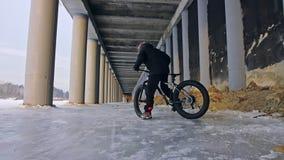 Cycliste extrême professionnel de sportif montant un gros vélo dans l'extérieur Tour de cycliste pendant l'hiver sur la glace de  banque de vidéos