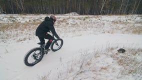 Cycliste extr?me professionnel de sportif montant le gros v?lo dans l'ext?rieur Le tour de cycliste en hiver dans le domaine de n clips vidéos