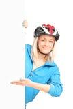 Cycliste féminin avec le casque se tenant derrière un panneau Images libres de droits