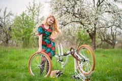Cycliste féminin avec le jardin blanc de bicyclette de vintage au printemps photos stock