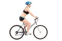 Cycliste féminin montant un vélo Photos stock