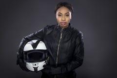 Cycliste féminin noir dans la veste en cuir tenant un casque Photographie stock libre de droits