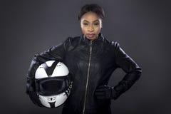 Cycliste féminin noir dans la veste en cuir tenant un casque Photo stock