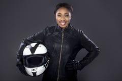 Cycliste féminin noir dans la veste en cuir tenant un casque Photographie stock